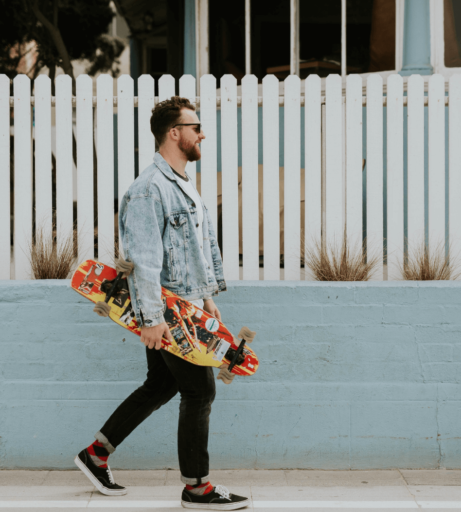 Man walking down the street with skateboard in hand