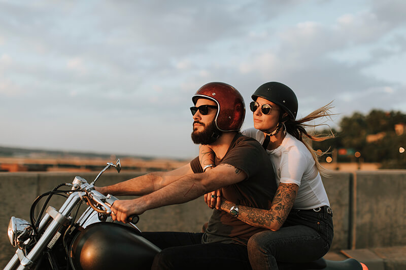 Couple on a motorbike, riding down the street