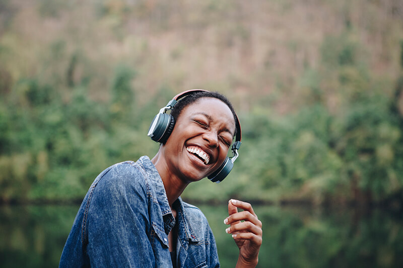 Woman listening to podcast with big earphones, laughing