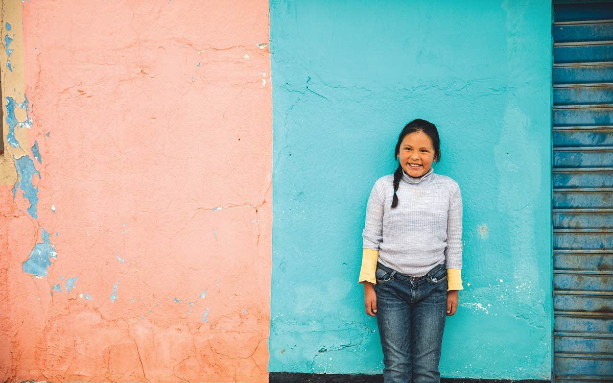 Child standing in front of a colorful wall