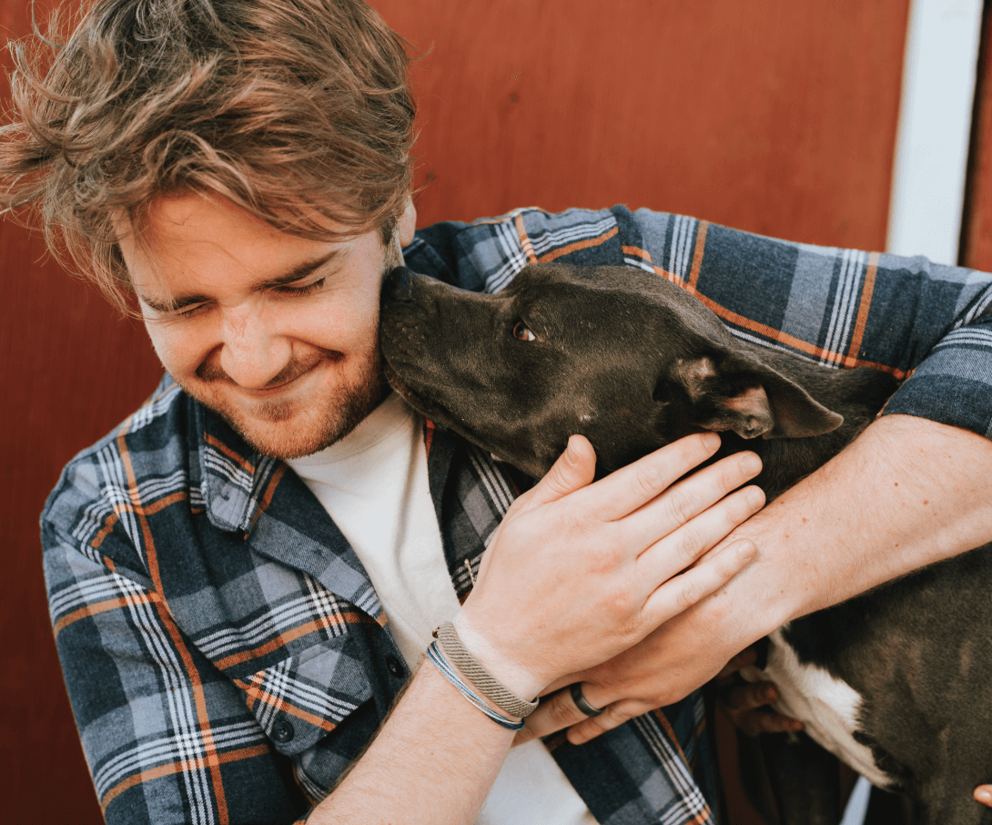 Man holding his dog while the dog licks his face