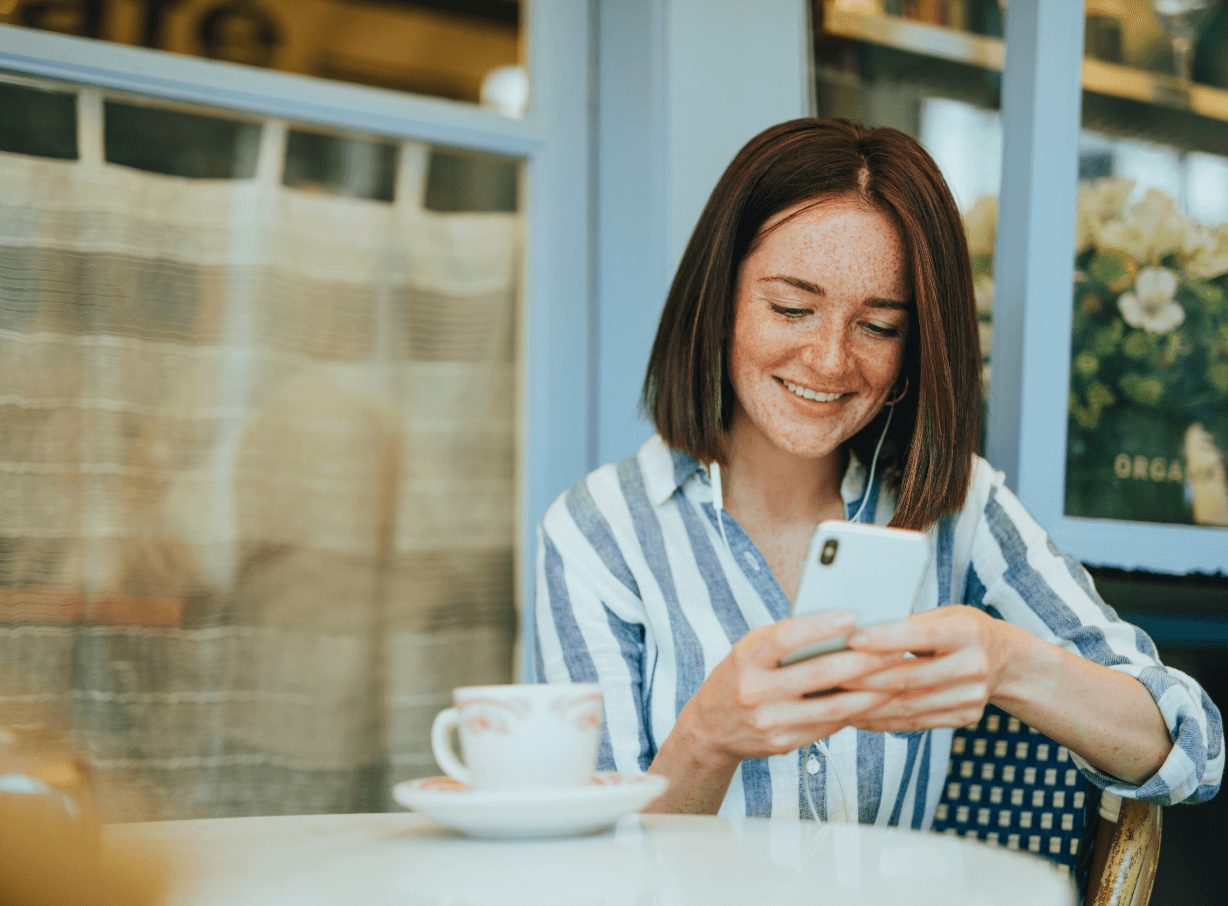 Woman sitting at coffee shot smiling and busy on her phone