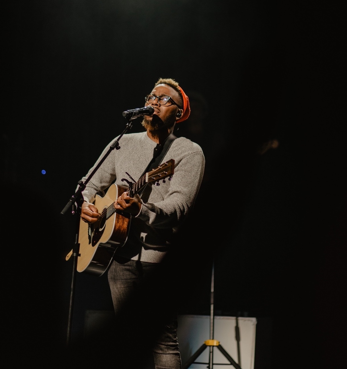 Man on stage singing and playing the guitar