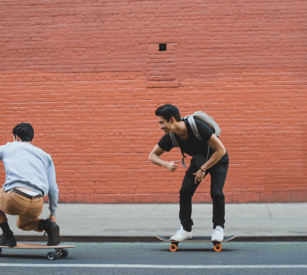 Two guys skateboarding down the road