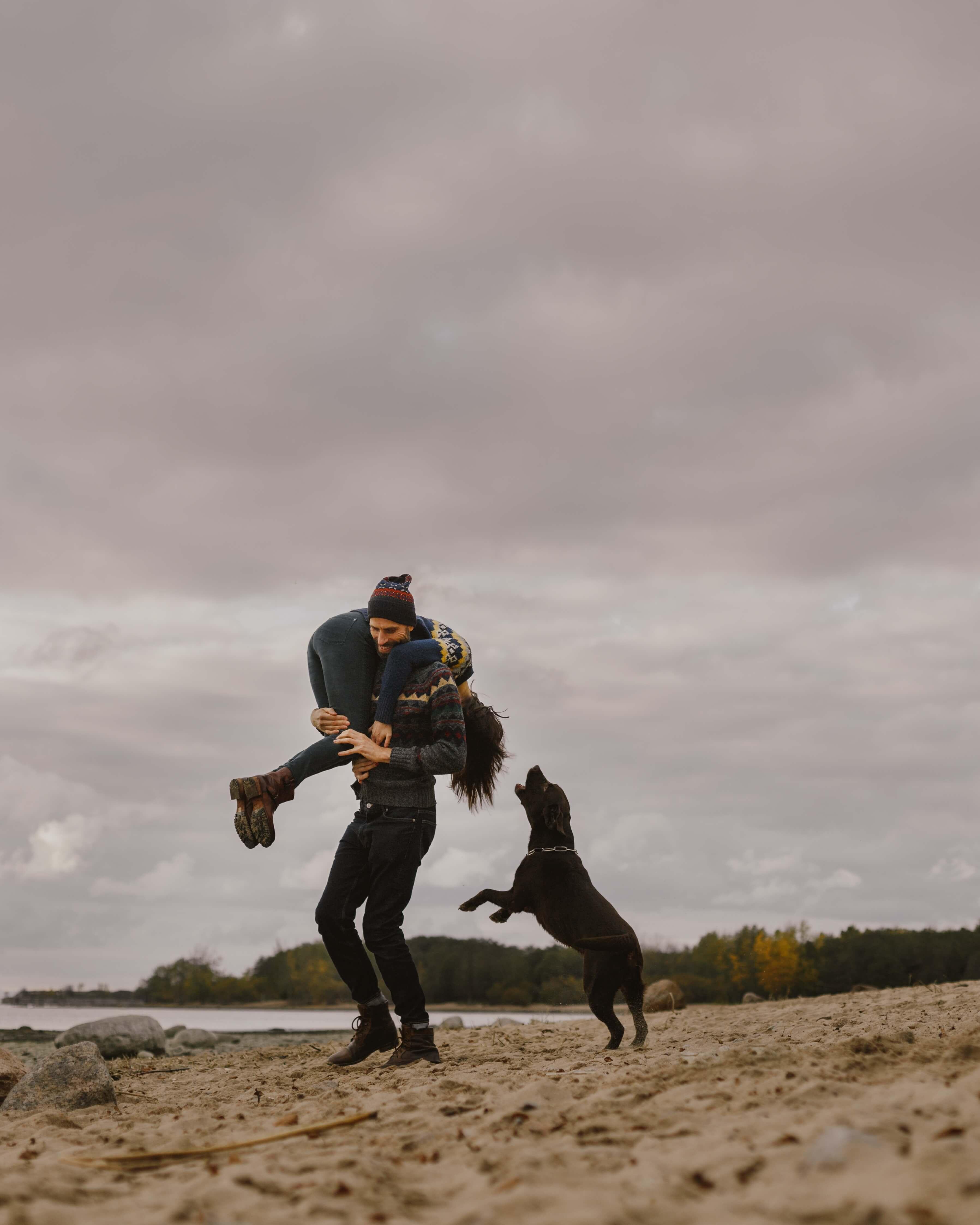 Man picking up woman while dog jumps