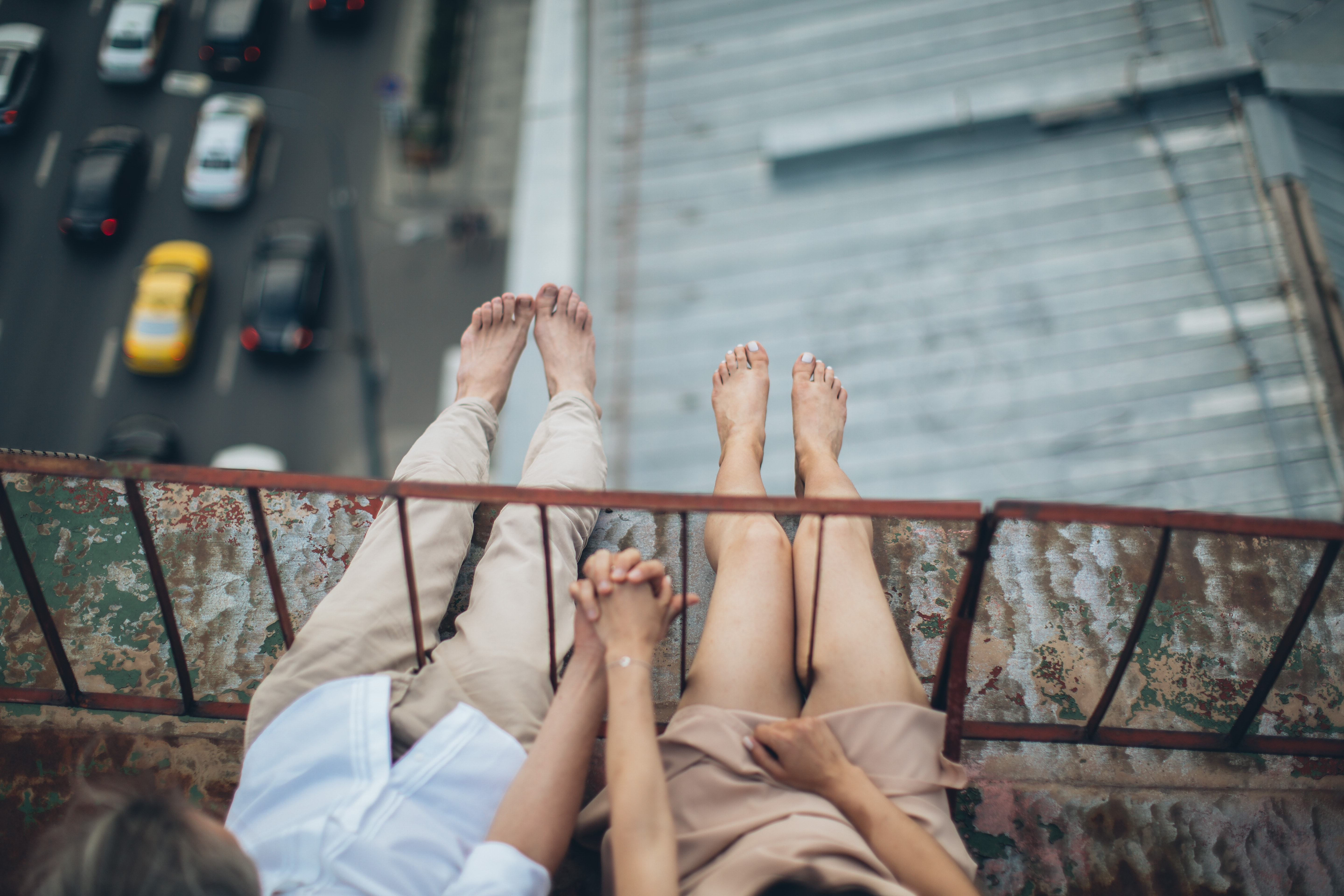 Couple with legs over the bridge holding hands