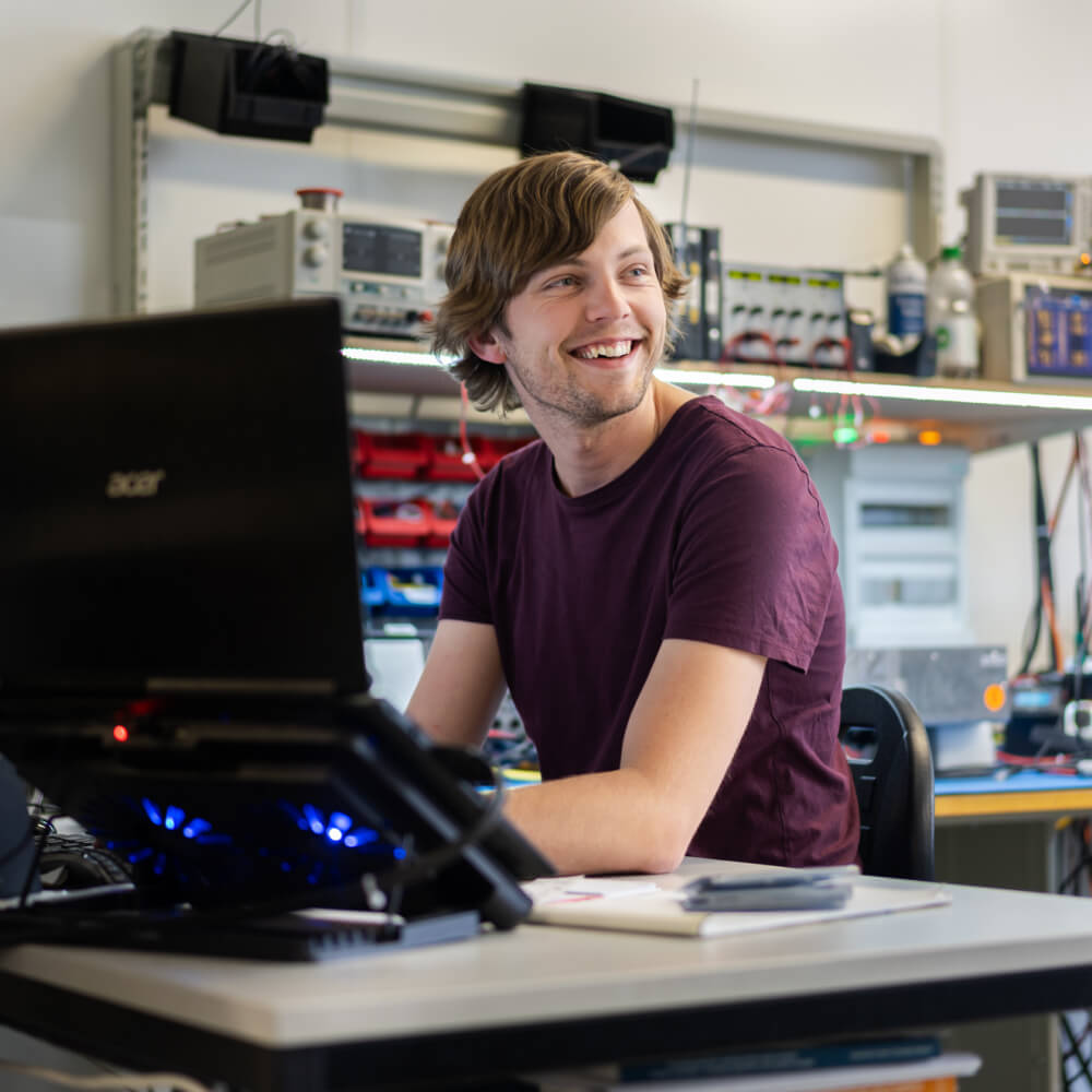 Employee of Heliox at his desk smiling