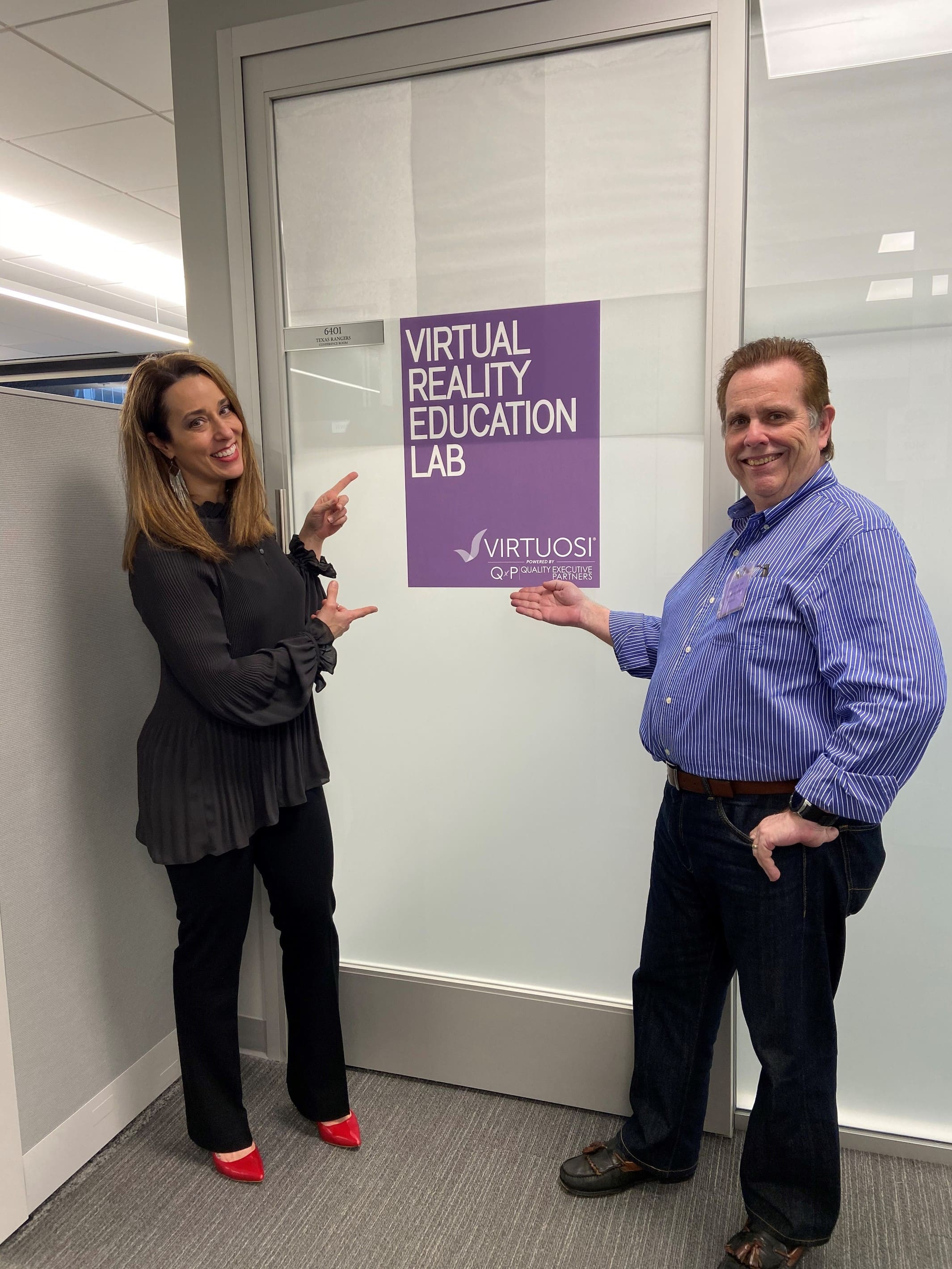 Two Virtuosi staff stand in front of the entrance to the Virtual Reality Education Lab.