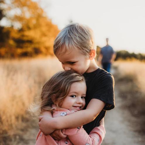 Young boy comforting his sister with a hug.
