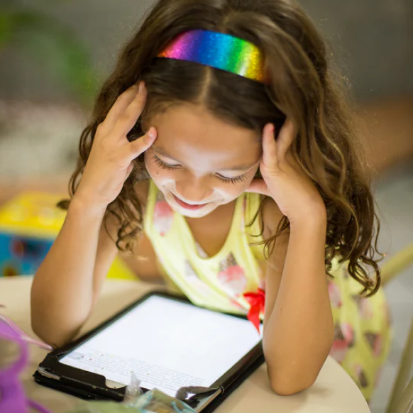 Young girl happily reading on a tablet