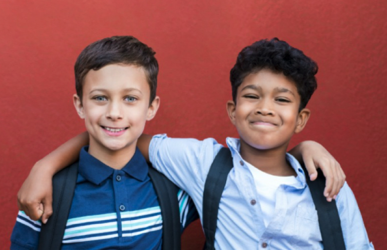 Two young boys smiling together for the camera.