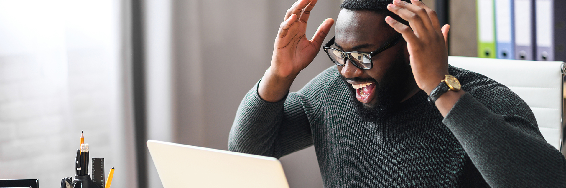 Excited Black man smiles at his computer like he won something