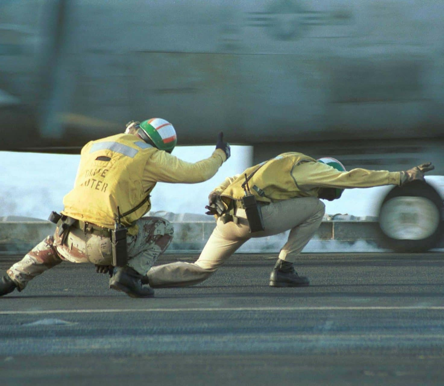 Two people working on an aircraft carrier