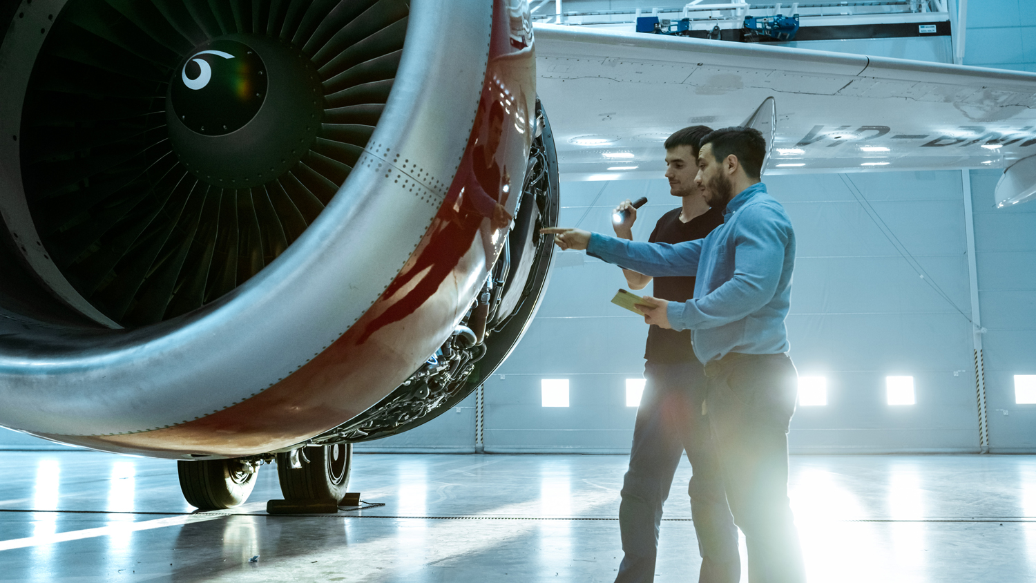 Two maintenance people work on an aircraft engine