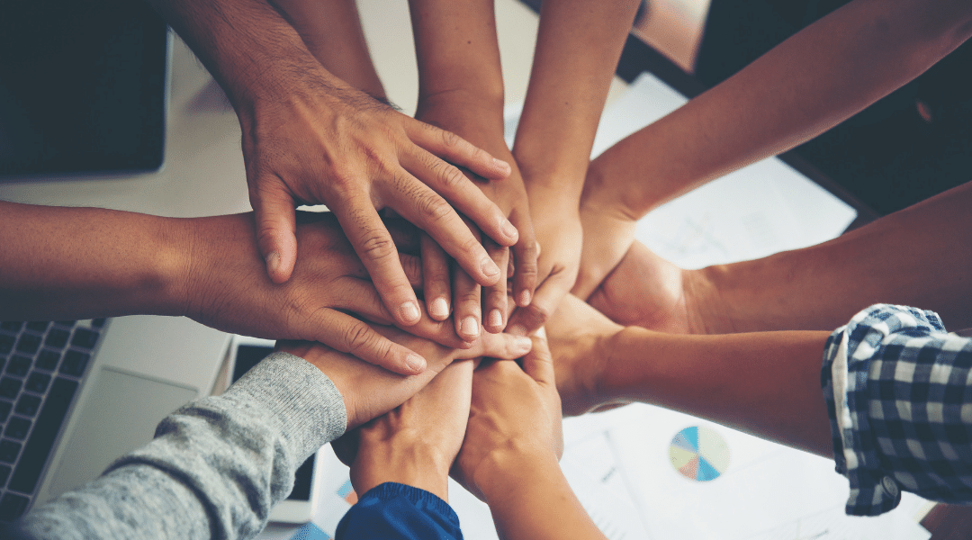 Picture of multiple people doing 'hands in' to represent collaboration