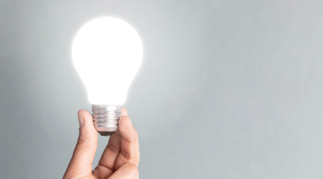 Person holding glowing lightbulb