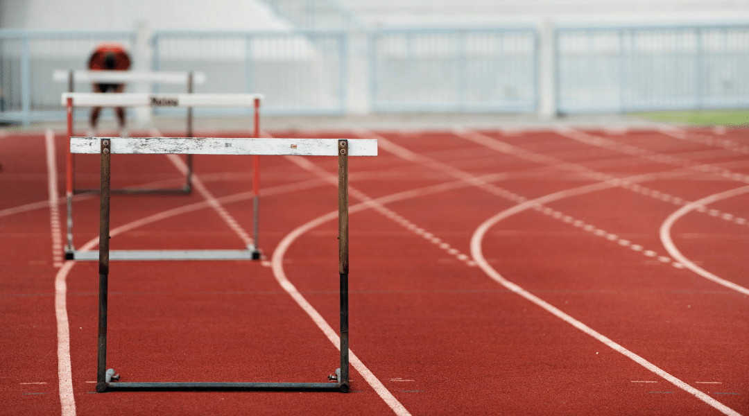 Athletic track with hurdles in foreground and blurry person doubled over at starting line