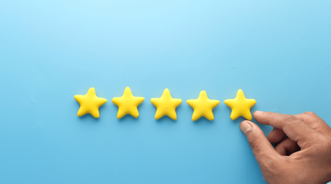 Hand arranging five yellow stars on a blue background