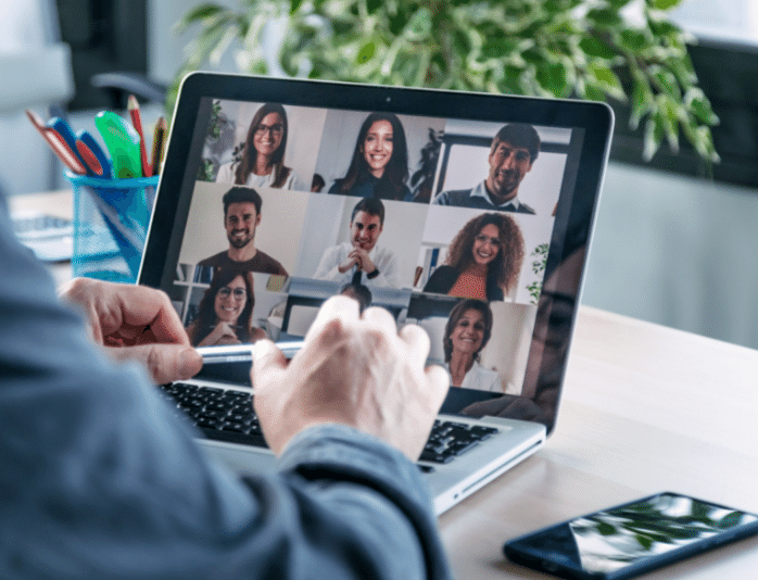Employee on laptop for virtual conference with multiple team members