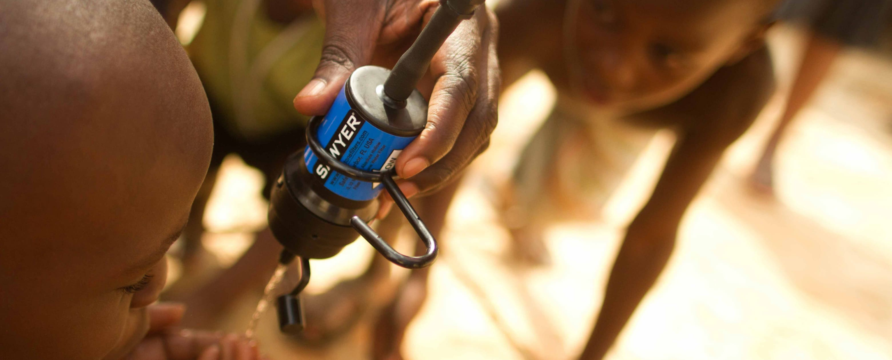 A Liberian child drinks from a Sawyer water filter.