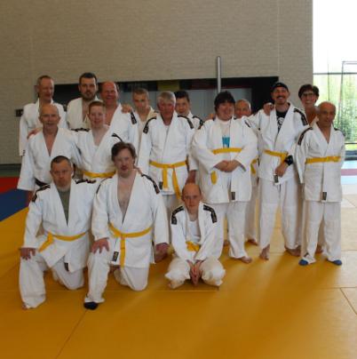 Groep personen in witte judo outfit op oranje mat