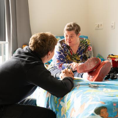 Begeleider houdt handen vast van cliente die op bed zit in campus t'Onzent