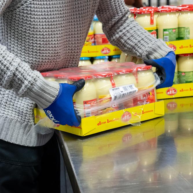 Detailfoto van persoon met blauwe handschoenen die potten mayonaise verpakt