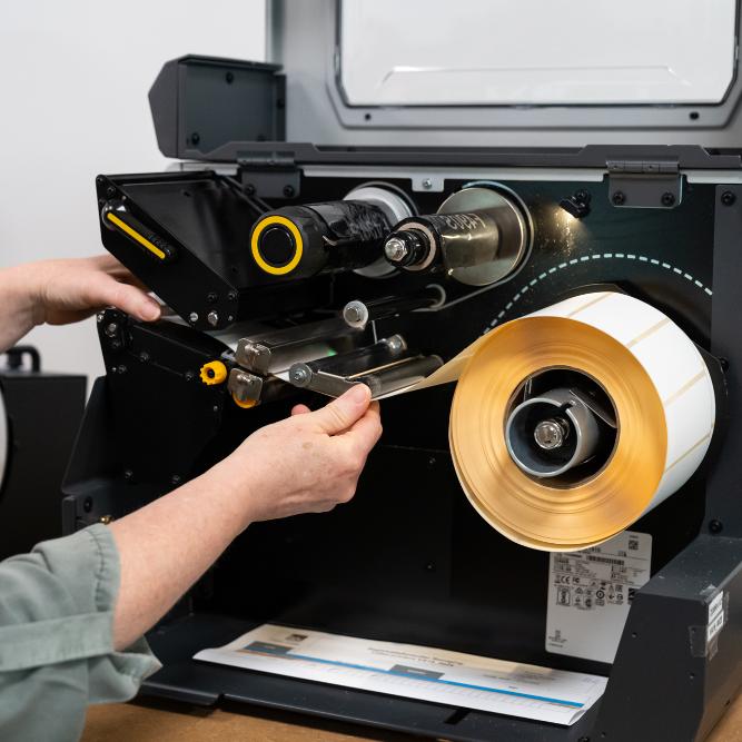 Detailfoto van een labelmachine met handen