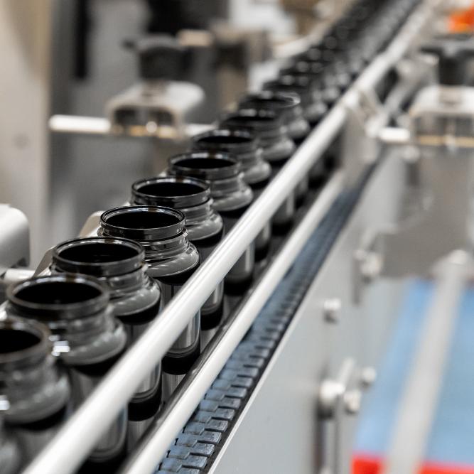 Detailfoto van lopende band met zwarte onderdelen op een rij