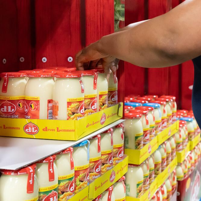 Handen die potten mayonaise in een display plaatsen