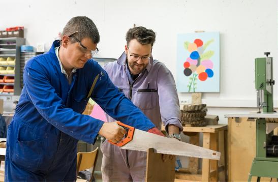 Twee personen die samen een stuk hout zagen in campus Flegado