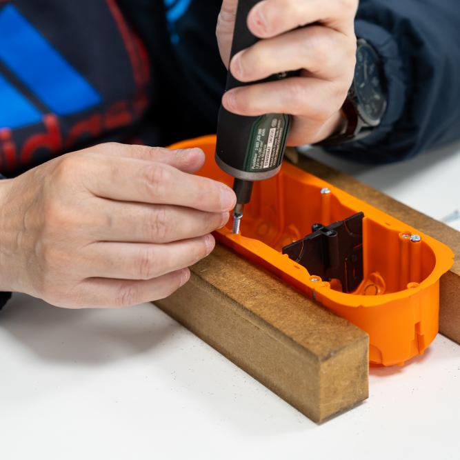 detailfoto van handen die een vijsje vastmaken en een oranje houder