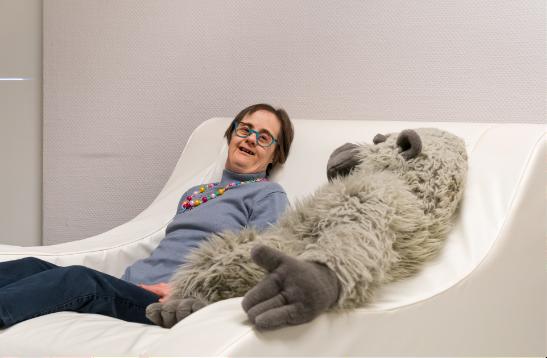 Cliënte die samen met een grote knuffelpop in een zetel ligt in campus Flexpack