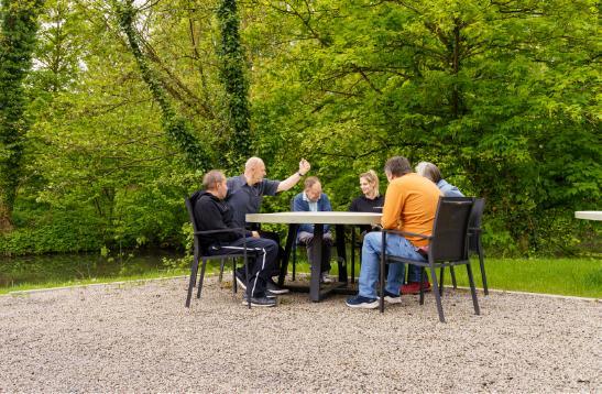 Verschillende personen zitten in de tuin aan een ronde tafel met elkaar te praten