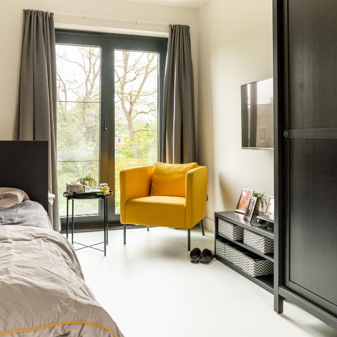 Overzichtsfoto van een persoonlijke kamer met bed en gele zetel in campus t'onzent