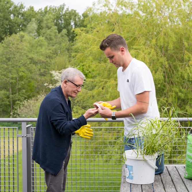 Cliënt en medewerker die samen planten verpotten in campus Flegado