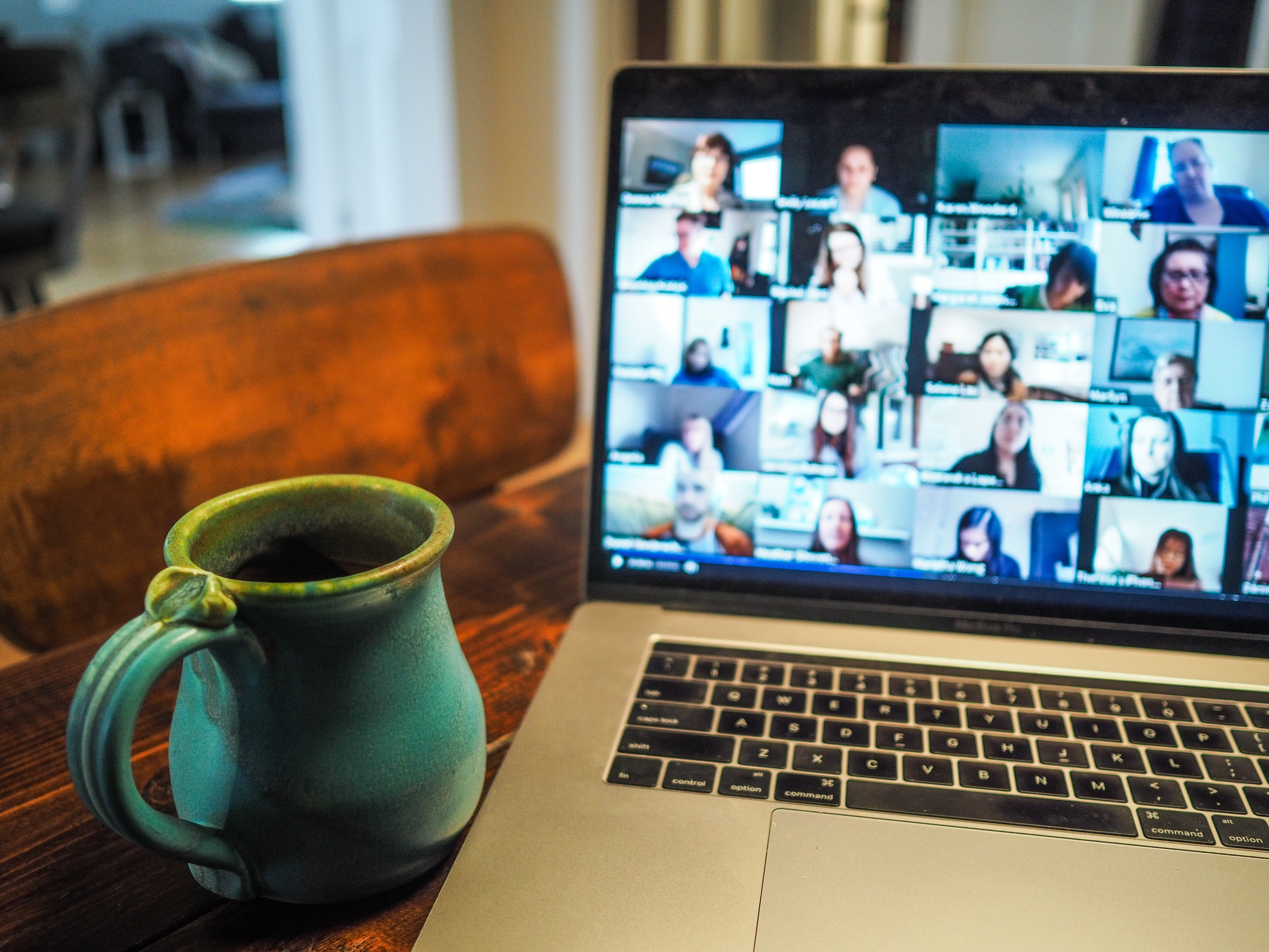 Video meeting on computer and coffee cup