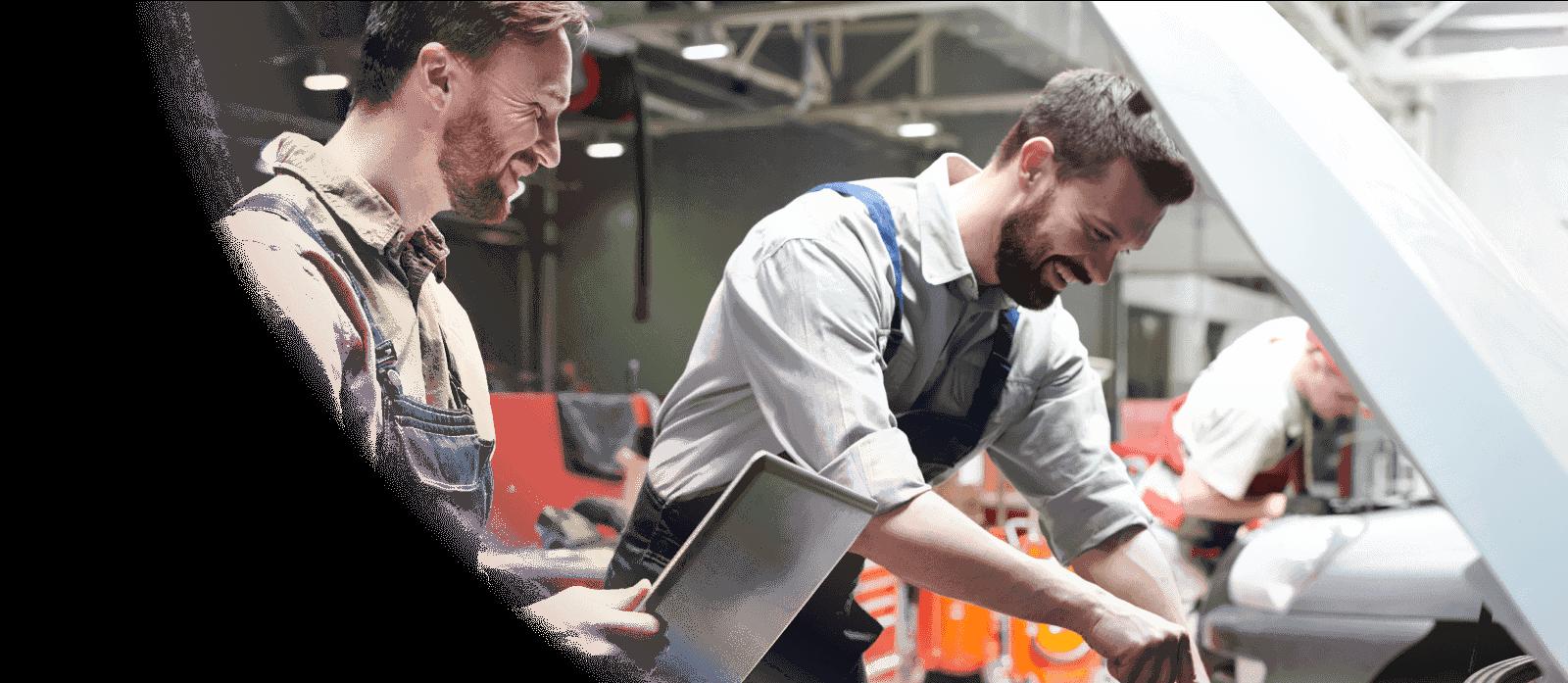 smiling men working on car engine