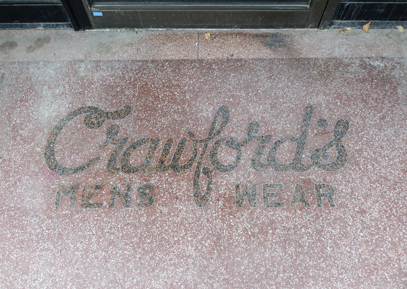 Pictured is the original Crawford's Menswear marble logo inlaid at the entrance of the building.