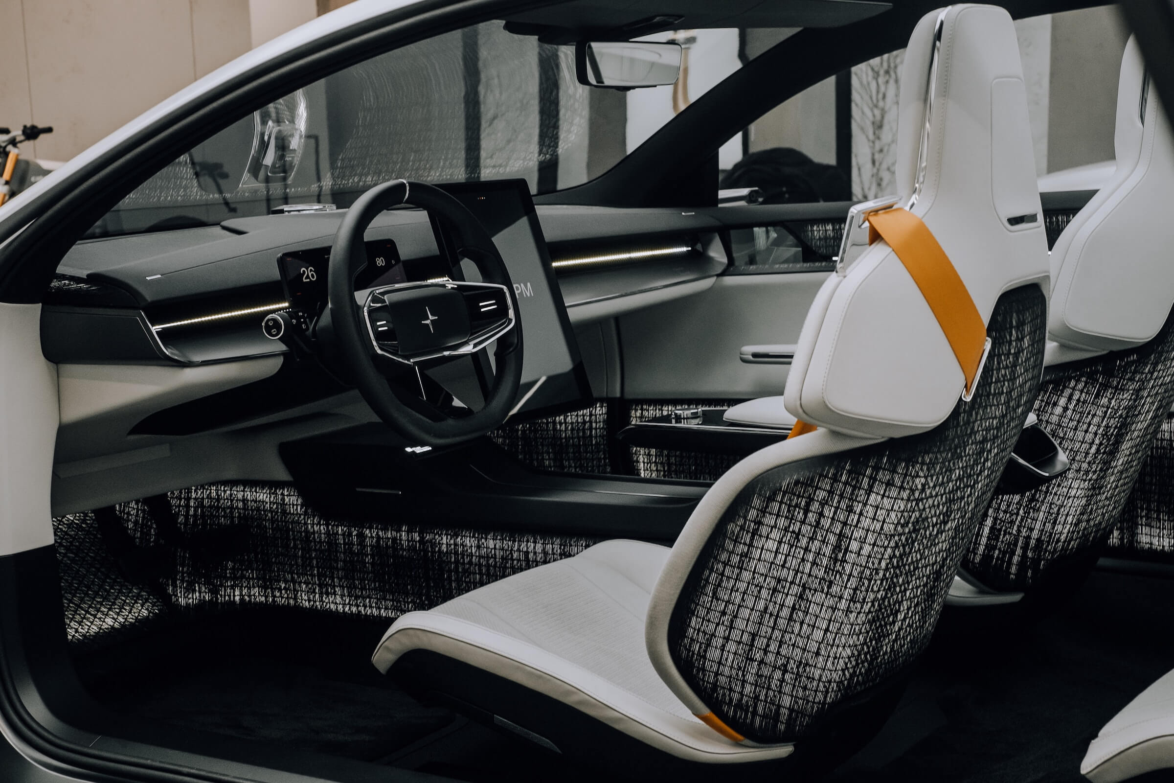 The interior of a car shot from the driver's side door showing the steering wheel and infotainment system