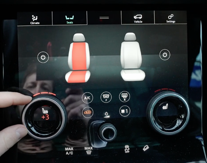Adjusting the seat temperature through a physical button while the illustration of the seat turns white to red