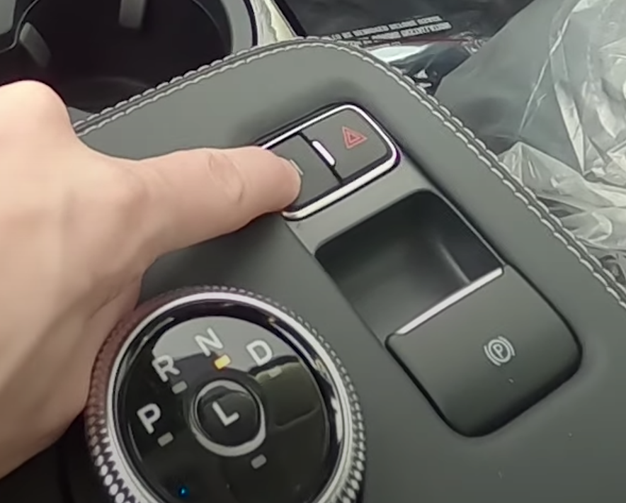 Image of buttons and dials underneath the infotainment system next to the user
