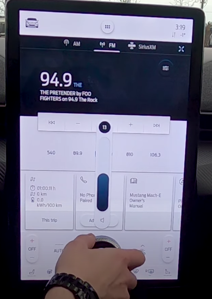 A user adjusting the volume from the big button in the middle of the infotainment system
