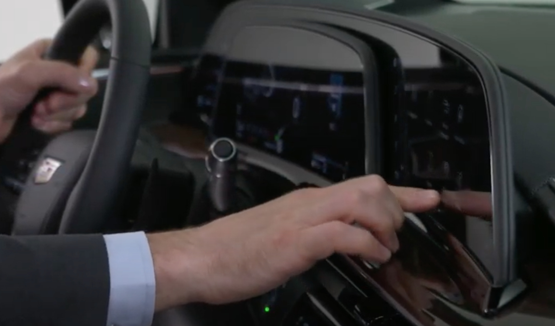 A photo of a user tapping on the infotainment screen showing how big the displays are