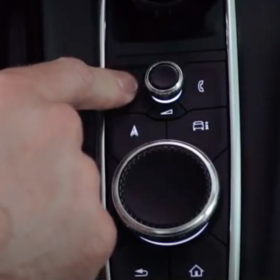 Photo of the buttons and dials next to a user underneath the infotainment system