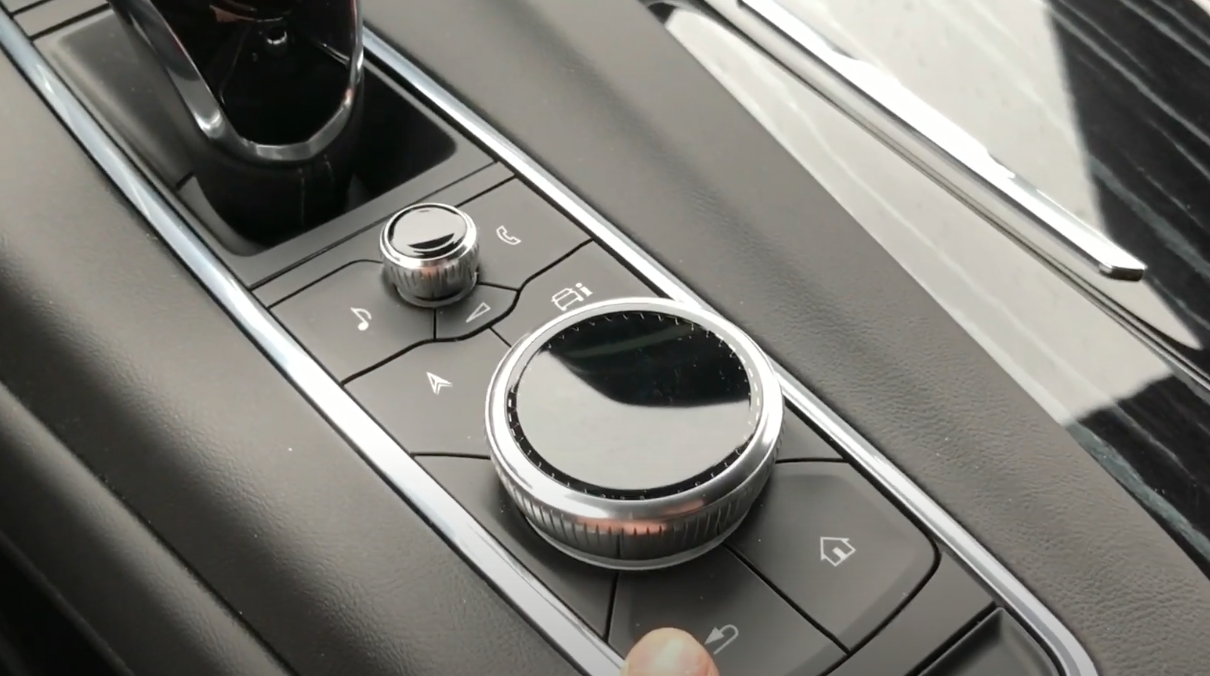Buttons and dials of the car next to the driver on their right underneath the infotainment system