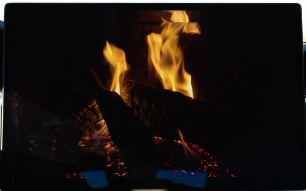 A video of a fireplace playing on the infotainment screen