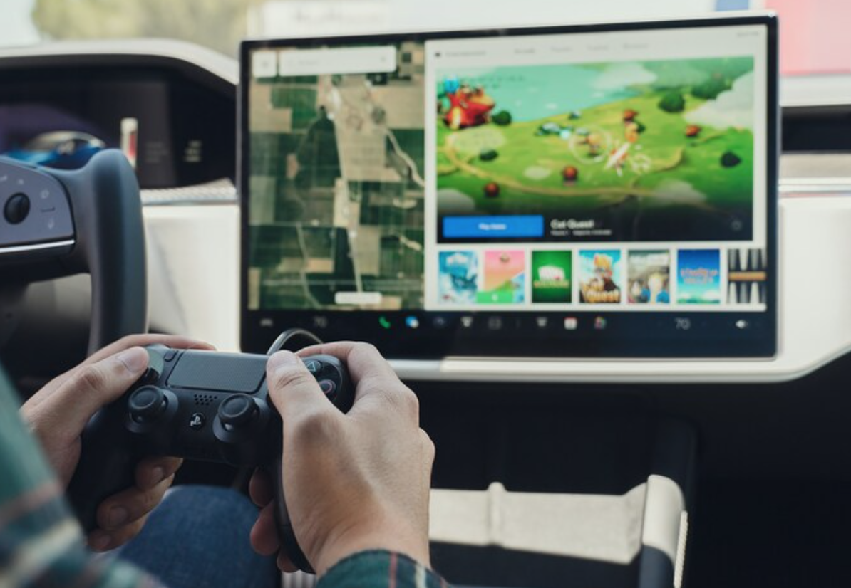 A user playing a game on the infotainment screen with a playstation controller