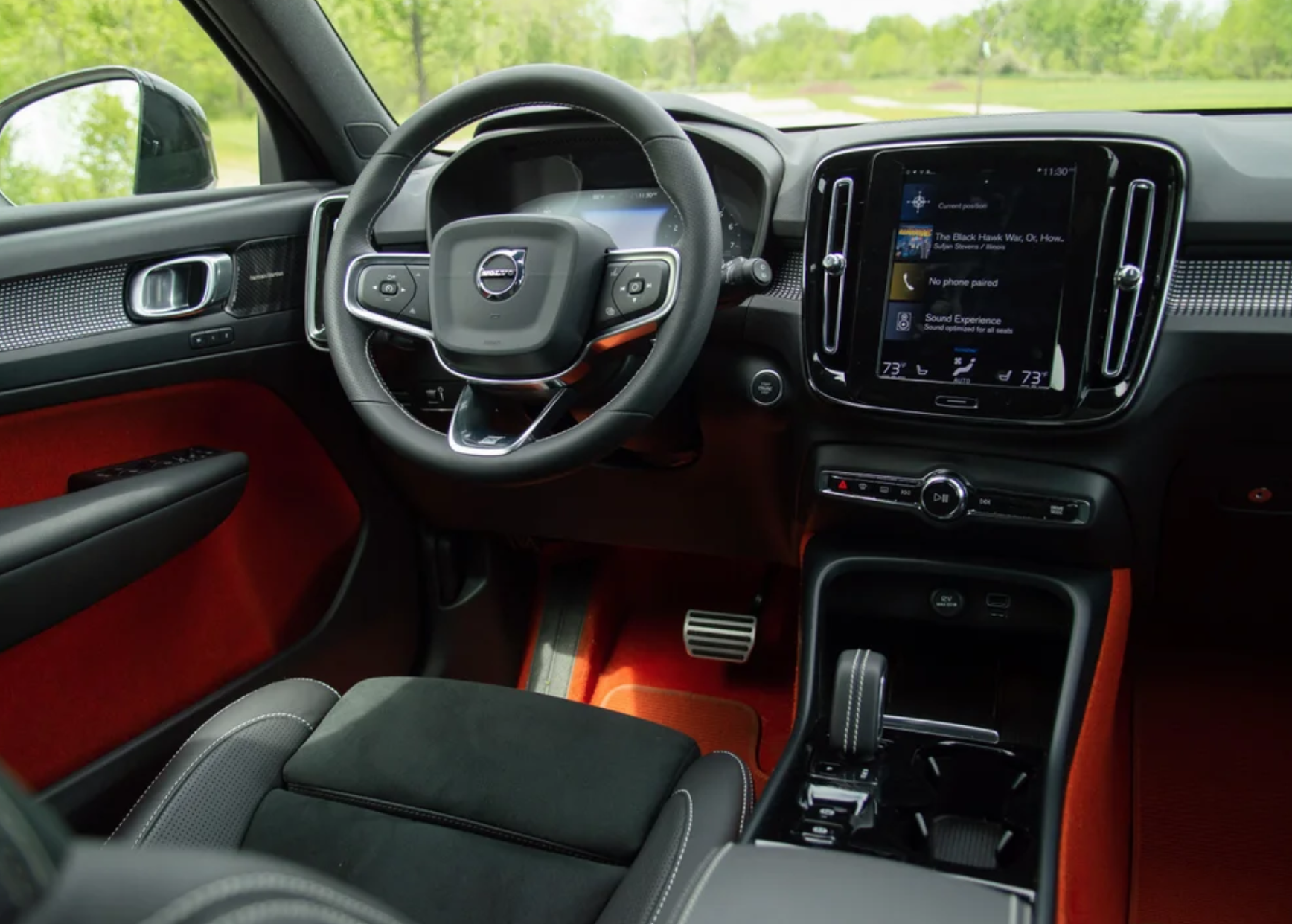 Photograph of the interior of a car showing touch screens, buttons and dials