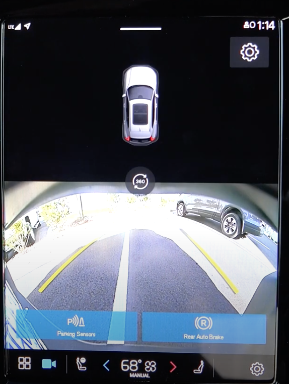 The rearview camera view on the infotainment system to assist with parking and the 3D model of a car